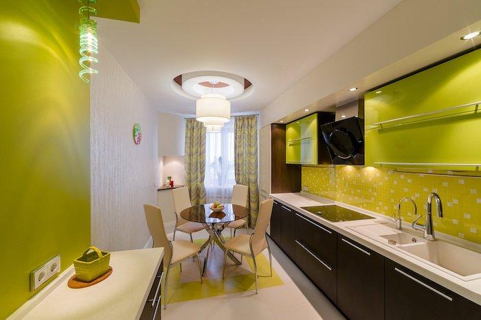 une cuisine en couleur limette et table ronde en verre au centre idée rangement cuisine