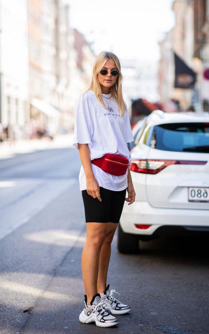 une femme blonde vetue en style casual chic avec des baskets tee shirt blan et sac rouge autour la taille