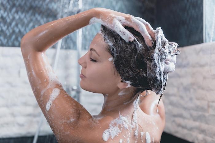 une femme dans la salle de bain en carrelage bleu qui frotte de shqmpoing sur ses cheveux