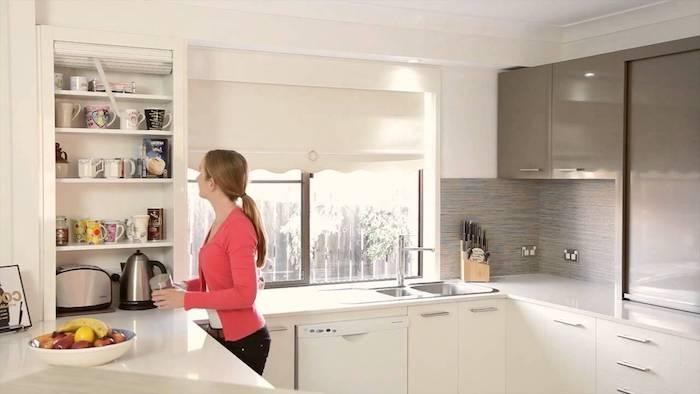 une femme dans une cuisine en forme de l avec des placards gris et surfaces lissantes