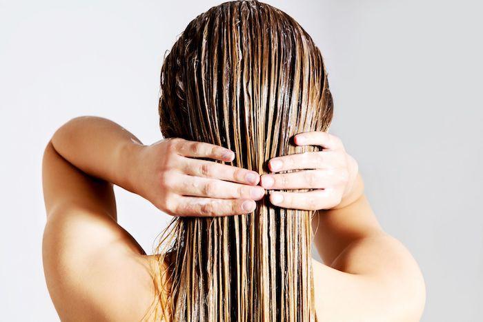 une femme en arrière applique de masque hydratant cheveux avec deux mains