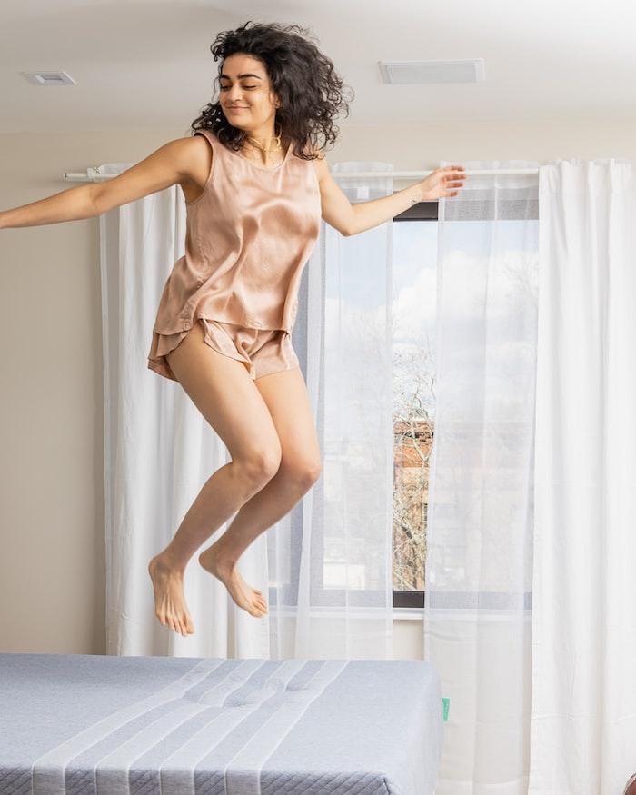 une femme en pijama satin saute sur le matelas devant un fenetre avec des rideaux blancs