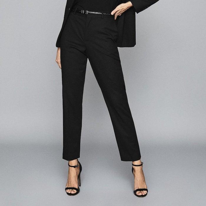 une femme en tenue noir avec des sandales et un pantalon longue jusqu aux chevilles