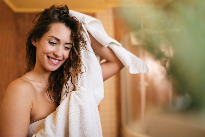 une femme qui frotte ses cheveux mouillés a l aide d une serviette blanche