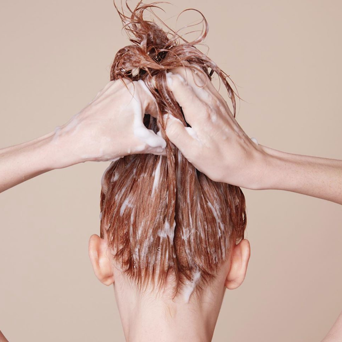 une femme qui tige ses cheveux onctués d un masque en haut avec des mains.jpg