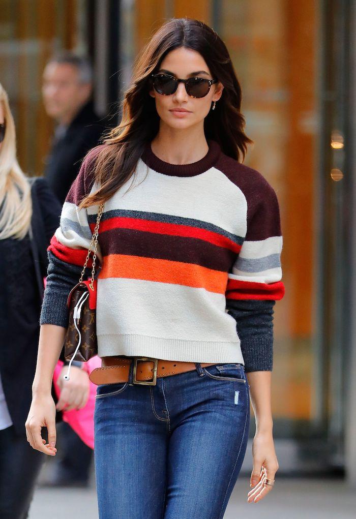 une femme vetue en style vestimentaire américain avec un jean et pull tricoté a rayes multicolores