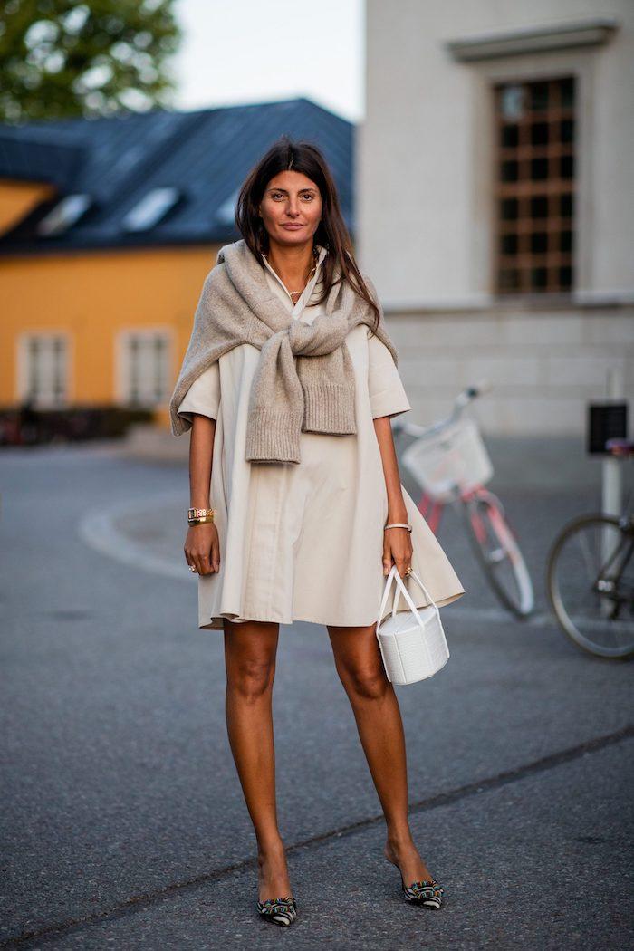 une femme vetue en tenue de soirée porte une robe beige des balerinas et un pull tricoté sur les épaules