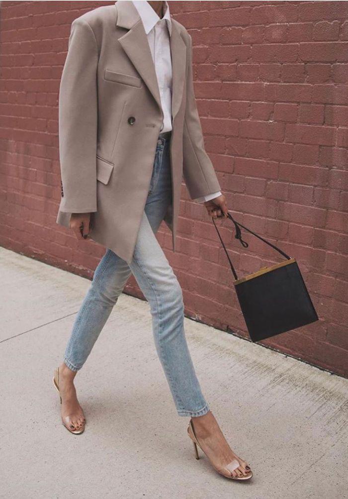 une femme vetue en tenue stylée et profesionnelle qui inclut jean veste ample et chemisier blanc