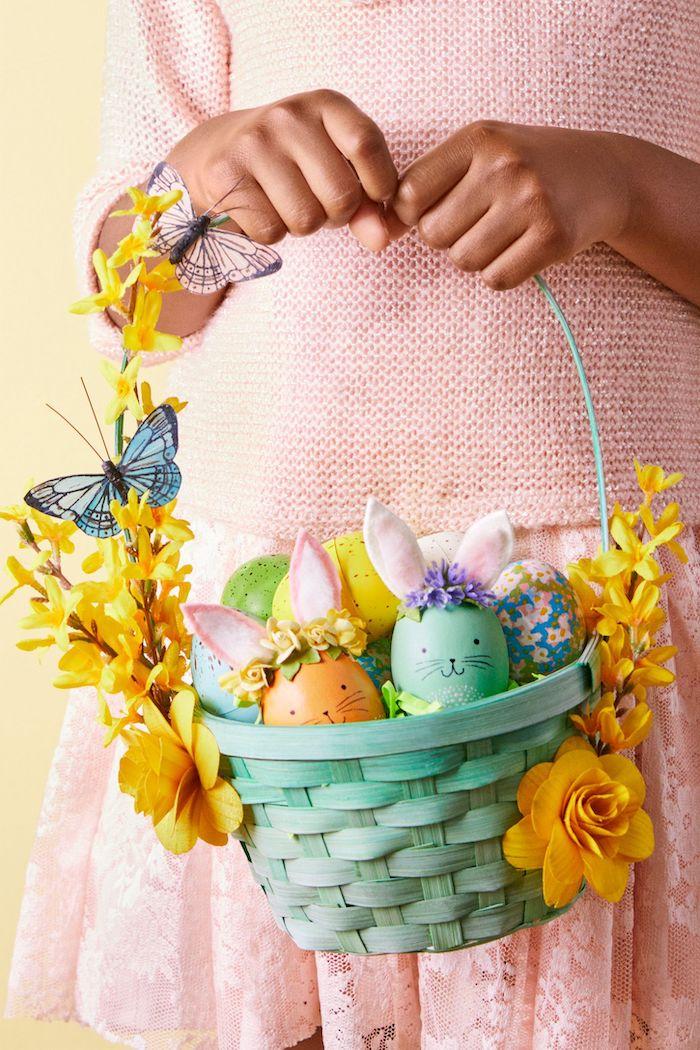 une fill ene robe rose tinet un panier de pâques en maternelle décoré des fleurs jaunes