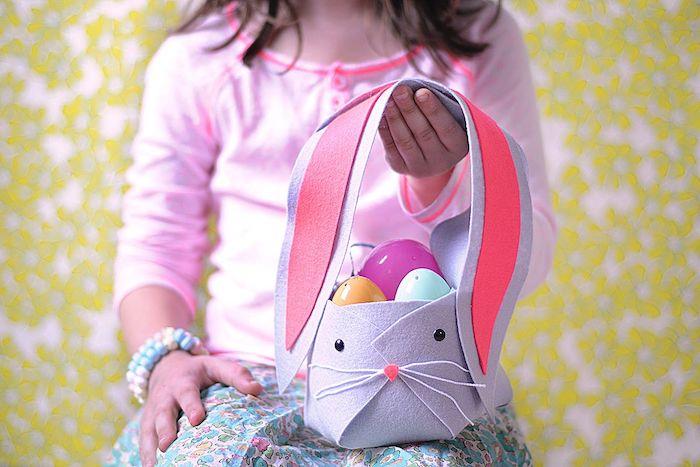 une fille qui tient une décoration de paque facile panier en forme de lapin rempli des oeufs en plastique
