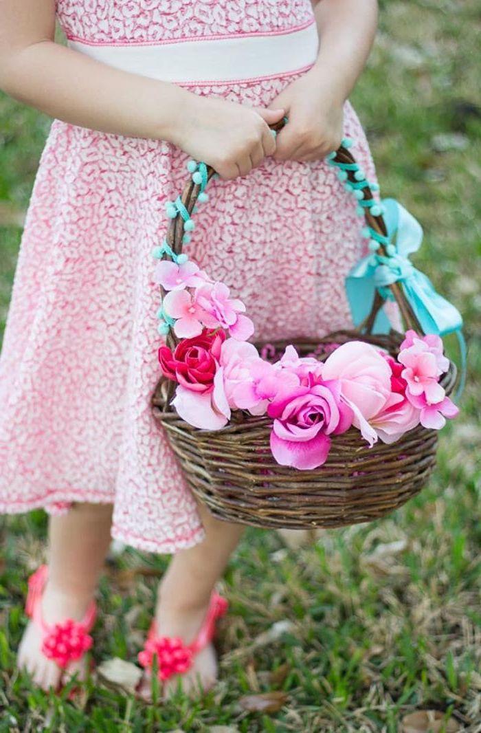 une fille vetue en robe rose tien un panier déco de paques a faire soi meme