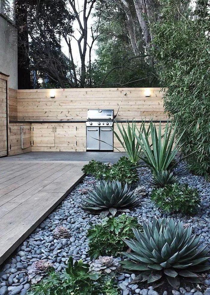 une idée de déco de massif avec galets et des succulents devant une maison moderne