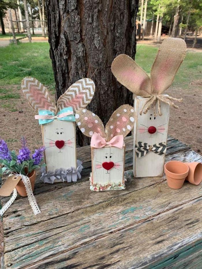 une idée de déco de paques diy avec des lapins élaborés de bois et de carton devant un grand arbre déco de pâques extérieure