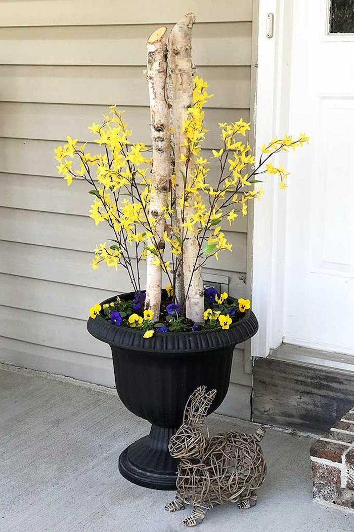 une idée de décoration de paques extérieure avec un grand cache pot noir et lapin décoratif en pailles
