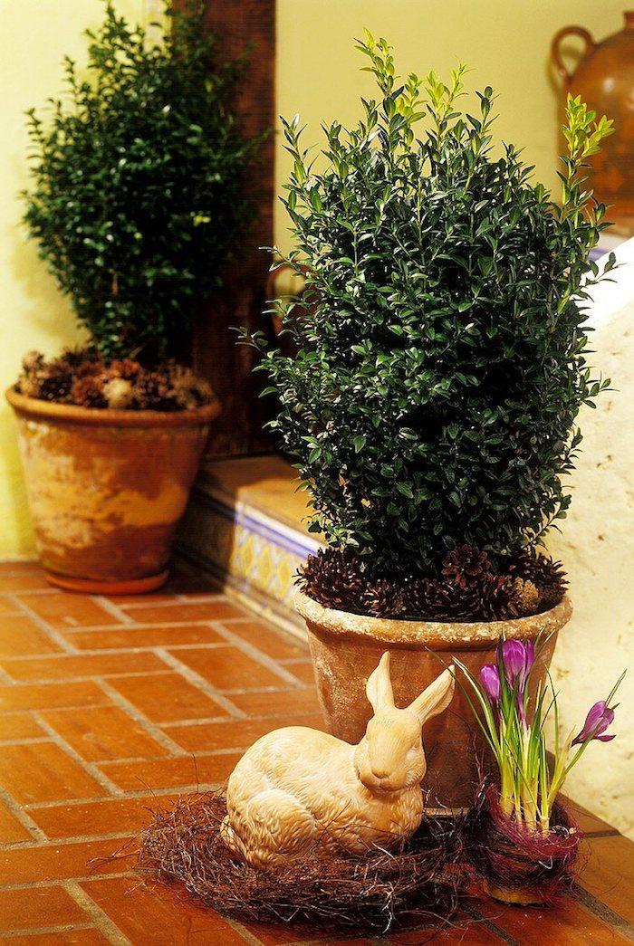 deco exterieure festive, sculpture de lapin dans nid et buis decoratifs en pot