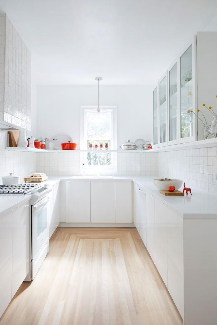 une idée de rangement dans la cuisine en u petite surfance en blanc avec des elements rouges