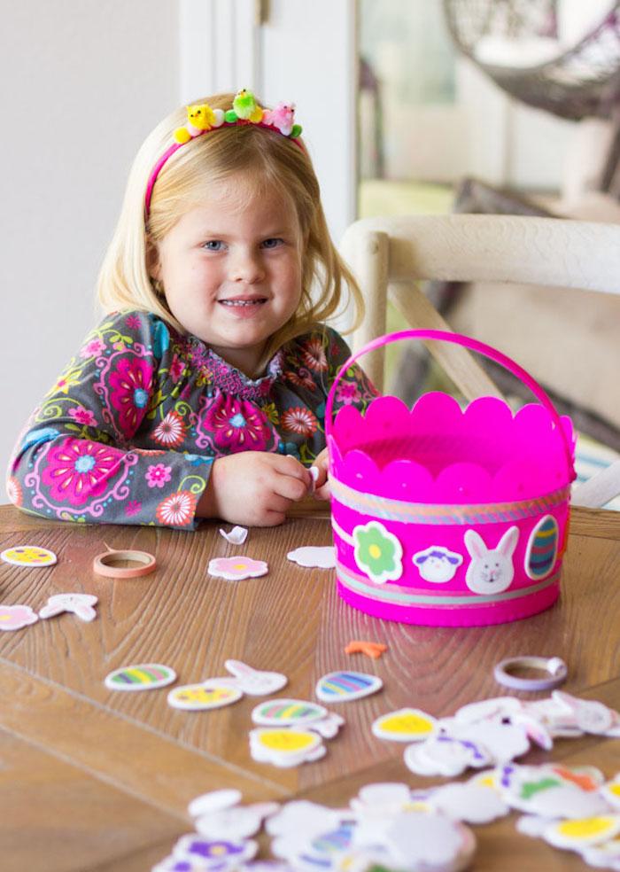 une jolie petite fille blonde qui fait un bricolage paques primaire avec un panier en plastique rose et des autocollants