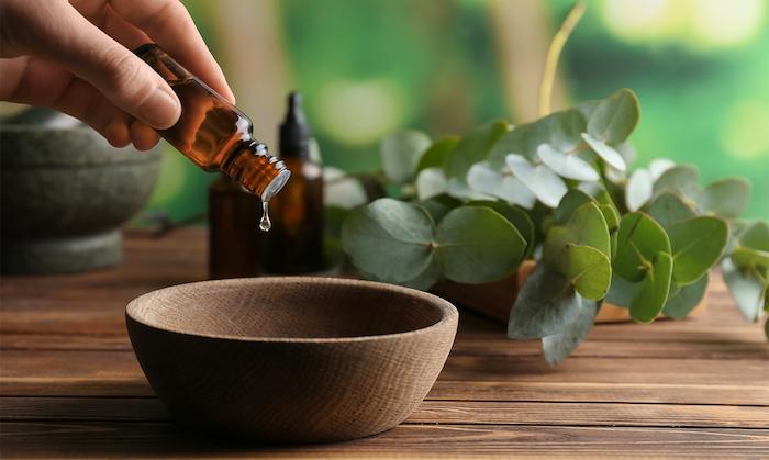 une main qui dégoutte de l huile essentiel dans un bol en bois huile cheveux secs