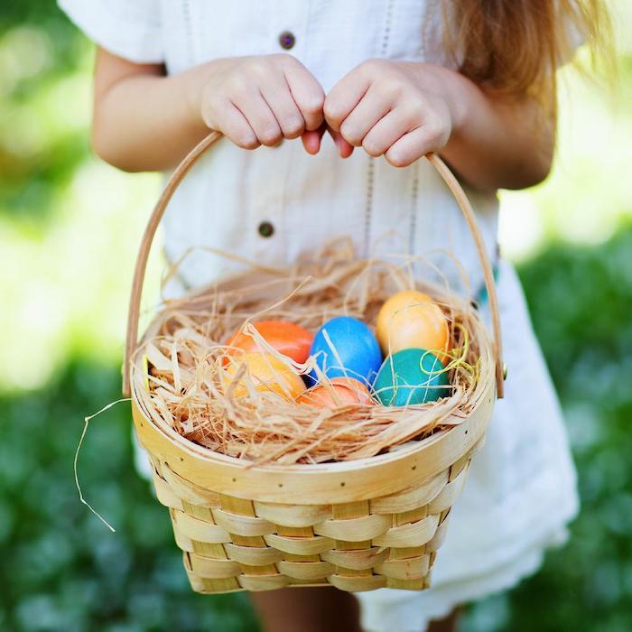 une petite fille tient un panierr tissée plein de l herbe fausse et des oeufs teints