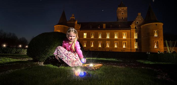une petitte fille qui collecte des oeufs dans le jqrdn devant un chateau