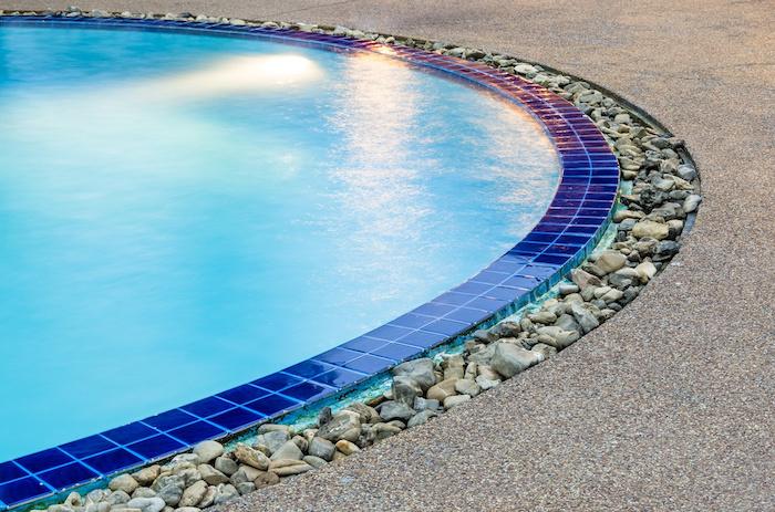 une piscine entourée d une bordure des pierres décoratives et des carreaux bleus
