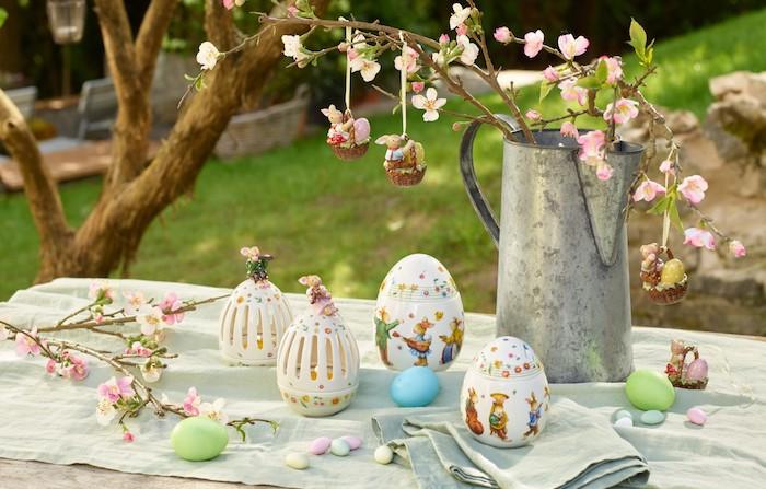 une table dans le jardin couvert d une nappe et décoré des oeufs et d un arrosoir vintage
