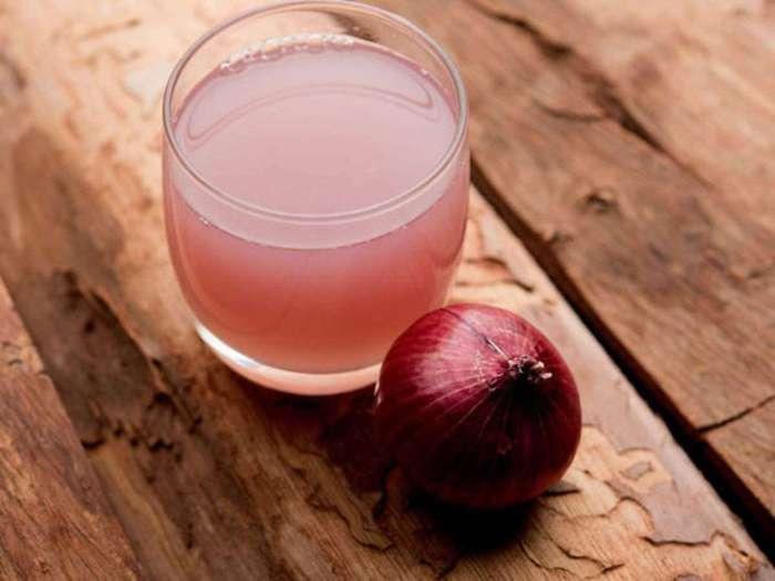 une tasse de jus d oignon sur une table en bois pour masque capillaire maison
