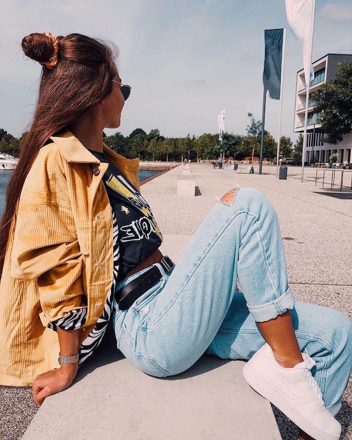une tenue streetwear femme avec jean blue clair baskets blanches et une veste jaune