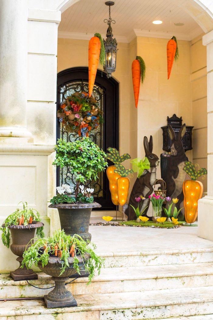 une véranda en beige décoré avec une deco de paques composée des lapins carottes suspendus du plafond et des pots a plantes vertes
