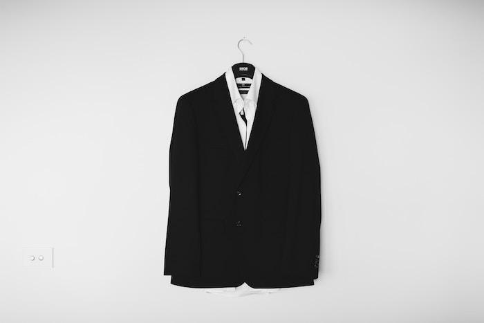 une veste noir style boyfriend accroché a un cintre avec un col blanc