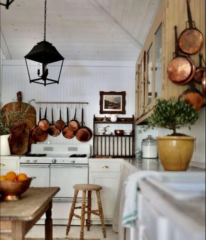 vaisselle ustensiles de cuisine cuivre dans cuisine blanche ilot et meuble haut bois accesnts boisés et plantes vertes