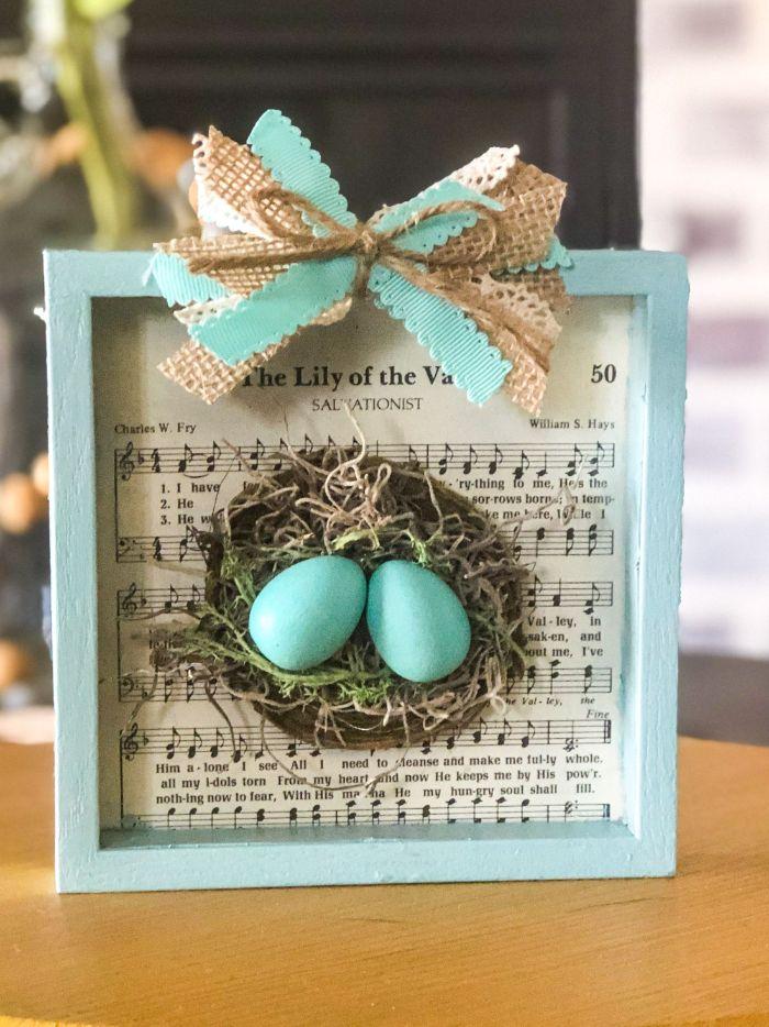 vieux cadre repeint de bleu avec deco de rubans et jute et fil un nid à l intérieur et oeufs bleus et fond musique diy paques