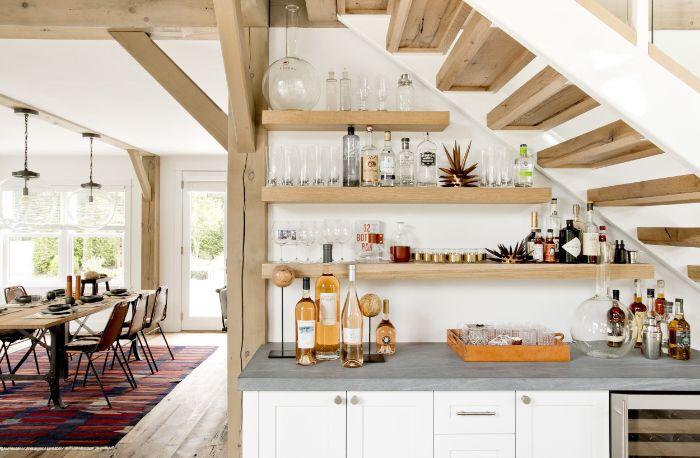 étagères ouvertes de bois sous escalier bois meuble cuisine blanc et plan de travail gris ouverture sur salle à manger