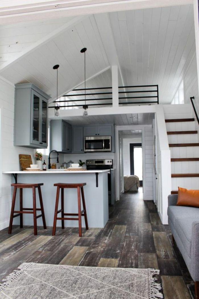 aménager une cuisine sous mezzanine de couleur gris clair ilot central et meuble gris credence lambris blanc parquet bois foncé fabouret bois