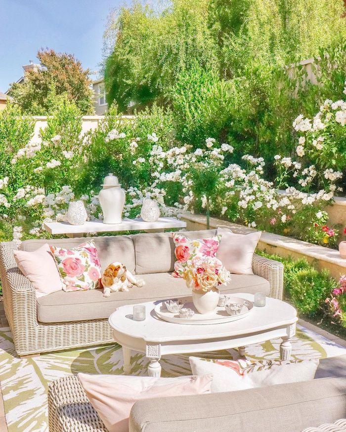 aménager un jardin planté des fleurs avec des canapés en rotin et des coussins beiges avec un petit chien au dessus