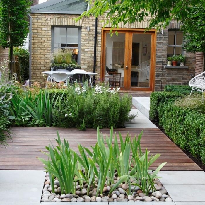 amenagement terrasse jardin façade maison briques végétation jardin galets blancs revetement terrasse bois