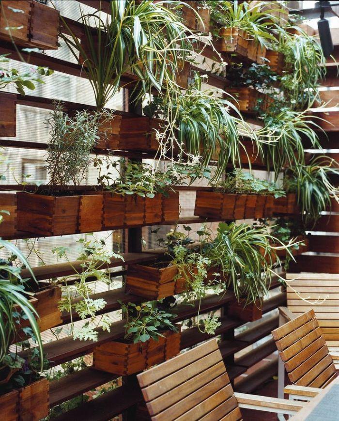 bacs de fleurs en vois avec des plantes vertes à l intérieur pour créer un paravent brise vue