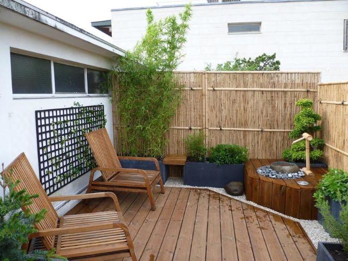 balcon terrasse de bois avec chaises boisés petit bassin de jardin arbustes verts et palissade bambou