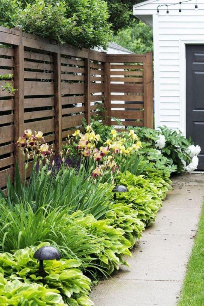 barrierre en palette ou autres planches de bois recyclées cacher bordure de jardin cour maison