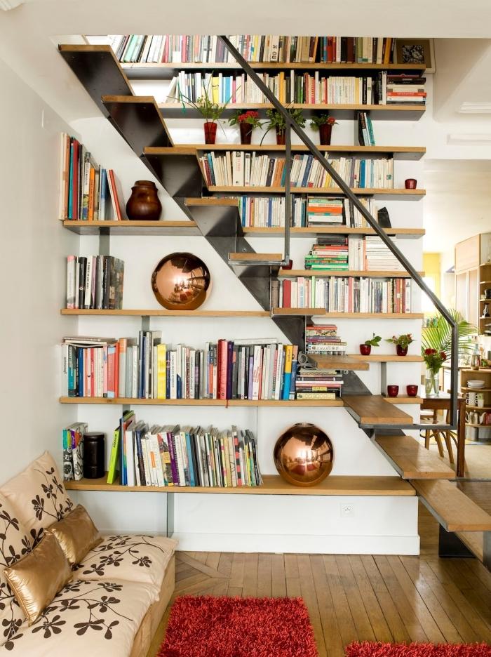 bibliothèque sous escalier banquette bois coussins dorés vase rose gold étagère bois clair tapis rouge