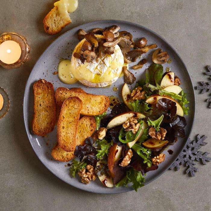camembert au four accompagnement avec de la salade verte des pommes et des noic dans une assiette violet deux bougies allumées a coté