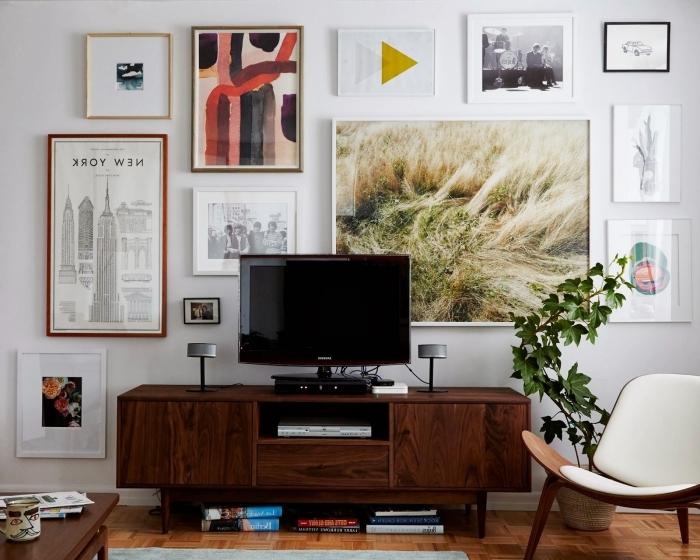 chaise fauteuil bois mur de cadres art abstrait poster idee deco meuble tv bois foncé plante verte