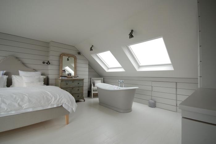 chambre sous pente avec baignoire autoportante éclairage moderne fenetre de toit lit miroir vintage