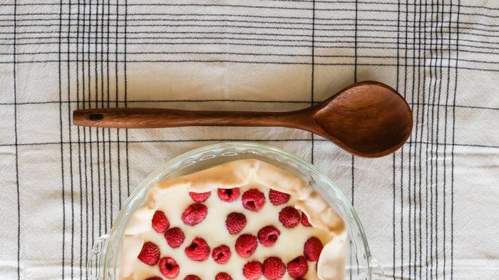 clafoutis aux framboises cuillère bois serviette blanc et noir préparation dessert pâte maison
