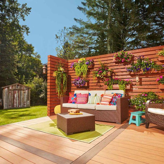 cloture bois originale décorée de pots de fleurs boisées aux végétaux colorés salon de jardin tressé terrasse composite