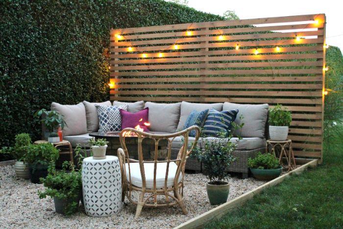 cloture en palette de bois décorée de guirlande lumineuse salon de jardin tressé sur gravier avec des plantes en pot
