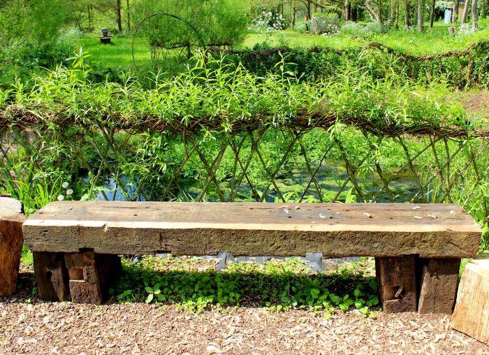 cloture vegetale de branches entrlacées et des feuillages banc de pierre près d un lac gazon vert