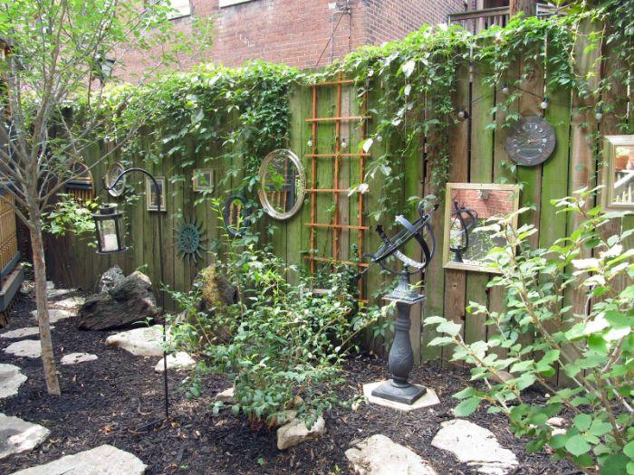 comment cloture un jardin avec des planches de bois envahies de lierre et vegetation deco exterieure miroirs et aautres accents deco