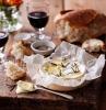 comment servir fromage camembert dans une boite en bois avec une verre de vin et du pain croustillant