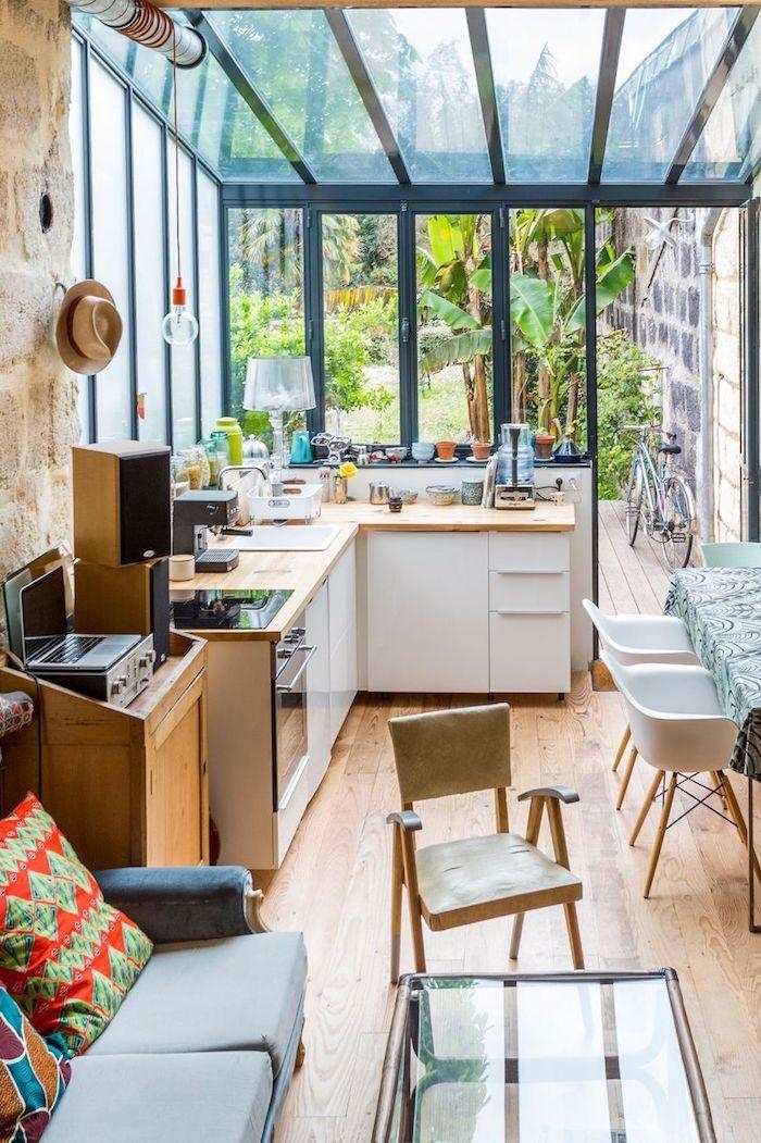 conseils de decoration veranda intérieur avec des coussins et plantes vertes derrierre des murs en verre